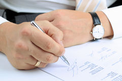 Businessman  sitting at office desk and  signing a contract. By pen Stock Photo