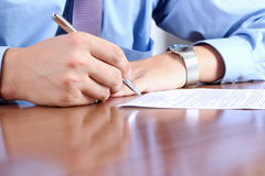 Businessman  sitting at office desk and  signing a contract  by. Pen Royalty Free Stock Photo