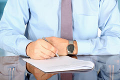 Businessman  sitting at office desk and  signing a contract  by. Pen Stock Photos