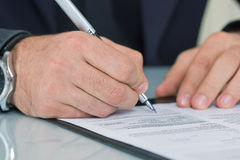 Businessman  sitting at office desk signing a contract Stock Photo