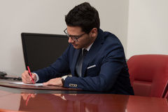 Businessman Sitting At Office Desk Signing A Contract Royalty Free Stock Photography