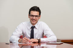 Businessman Sitting At Office Desk Signing A Contract Stock Photos