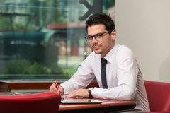 Businessman Sitting At Office Desk Signing A Contract Royalty Free Stock Image