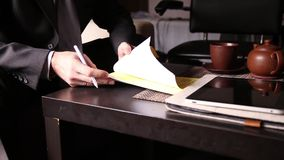 Businessman sitting office desk signs a bill comparing them, with the pc tablet. close-up hands of a man and a fountain stock footage