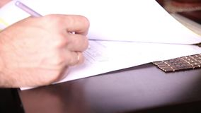 Businessman sitting office desk signs a bill comparing them, with the pc tablet. close-up hands of a man and a fountain stock video footage
