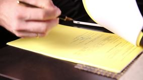 Businessman sitting office desk signs a bill comparing them, with the pc tablet. close-up hands of a man and a fountain stock video