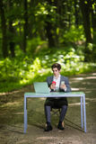 Businessman sitting at the office desk work at laptop computer and cup of coffee use mobile phone on road of green forest park. Bu Stock Images