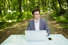 Portrait of Businessman sitting at the office desk work at laptop computer in green forest park. Freelancer portrait working on of Stock Photos