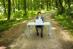 Businessman sitting at the office desk work at laptop computer in green forest park. Freelancer working on office table in green p Royalty Free Stock Photos