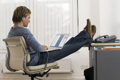 Businessman sitting in office with feet up on desk, using laptop in lap, profile Stock Photos