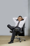 Businessman sitting in office, hands behind head Royalty Free Stock Image