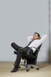 Businessman sitting in office, hands behind head Stock Photos