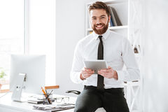 Businessman sitting in office while holding tablet . Image of young businessman sitting in office while holding his tablet computer Stock Photo