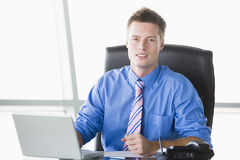 Businessman sitting in office with laptop Royalty Free Stock Image