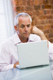 Businessman sitting in office on laptop Royalty Free Stock Image