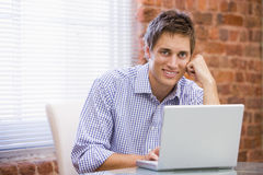 Businessman sitting in office with laptop smiling Royalty Free Stock Images