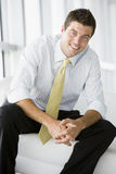 Businessman sitting in office lobby smiling Stock Photo