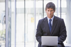 Businessman sitting in office lobby using laptop Stock Photos