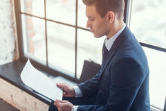 Businessman sitting in office reading contract documents Royalty Free Stock Photos