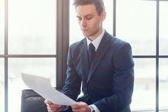 Businessman sitting in office reading contract documents Stock Images