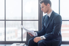 Businessman sitting in office reading contract documents Stock Photo