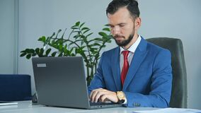Businessman Sitting In Office And Typing On Laptop