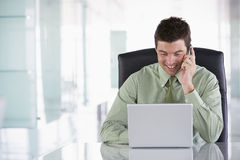 Businessman sitting in office using cellular phone Royalty Free Stock Images
