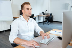 Businessman sitting in office and using computer Royalty Free Stock Images