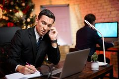 Businessman sitting in office and working on New Year`s Eve. He`s talking to someone on the phone. Against the background his colleague sits and stands a Royalty Free Stock Photo