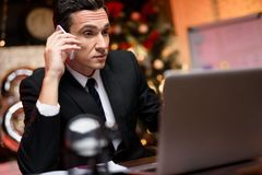 Businessman sitting in office and working on New Year`s Eve. He`s talking to someone on the phone. Against the background his colleague sits and stands a royalty free stock image