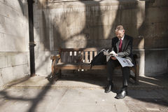 Businessman sitting on outdoor bench reading newspaper Royalty Free Stock Photography