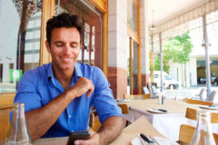 Businessman sitting at outdoor cafe with mobile phone Royalty Free Stock Photography