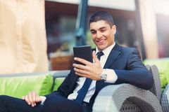 Businessman sitting at an outdoor cafe using a digital tablet Stock Photography