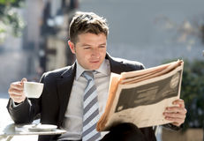 Businessman sitting outdoors for breakfast pause morning reading news in newspaper having coffee Royalty Free Stock Photography