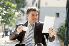 Businessman sitting outdoors in coffee break holding cup and digital tablet pad checking onl�ne news Stock Photos