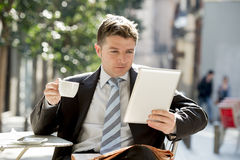 Businessman sitting outdoors in coffee break holding cup and digital tablet pad checking onl�ne news Stock Images