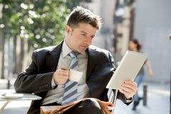 Businessman sitting outdoors in coffee break using digital tablet pad checking onl�ne news Stock Photo