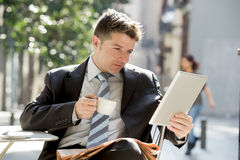 Businessman sitting outdoors in coffee break using digital tablet pad checking onl�ne news Stock Photo