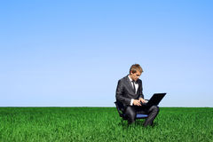 Businessman sitting outdoors with laptop computer Stock Photography