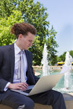 Businessman Sitting Outdoors With Laptop. And papers Stock Photos