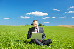 Businessman sitting outdoors thinking Royalty Free Stock Images