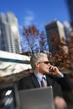 Businessman sitting  outside talking on cellphone with buildings Stock Image