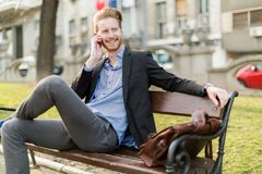 Businessman sitting on a park  bench while talking on the phone Royalty Free Stock Photography
