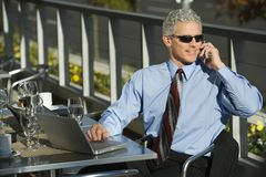 Businessman sitting at patio table otuside with laptop and talking stock photo