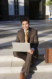 Businessman sitting on pavement steps, using laptop, smiling, front view, portrait Stock Photography