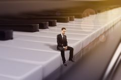 Businessman sitting on piano keys. Young european businessman sitting on abstract bokeh piano keys. Musician concept. 3D Rendering royalty free illustration