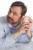Businessman sitting with a piggy bank Royalty Free Stock Image
