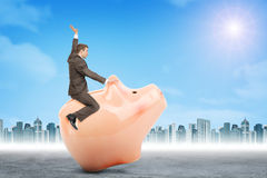 Businessman sitting on piggy bank, side view. Businessman sitting on piggy bank on nature background Stock Image