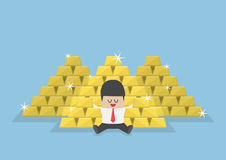 Businessman sitting with a pile of gold bars Stock Images