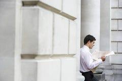 Businessman Sitting On Pillar Reading Newspaper Stock Image